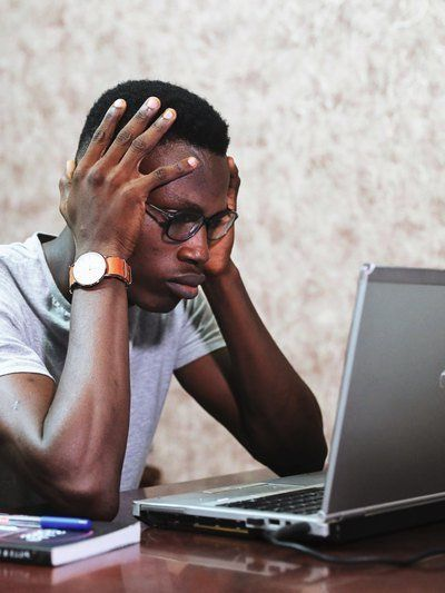 Man holding head seated behind laptop