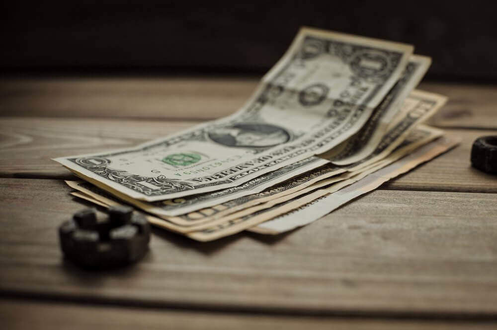 Small stack of US dollar bills | Guide My Growth