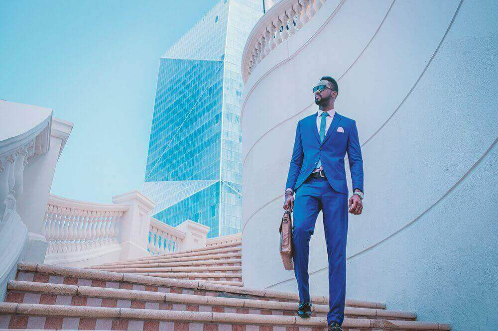 Man in a blue suit walking down stairs in a business district | Guide My Growth