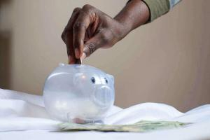 Person putting money into a piggy bank | Guide My Growth