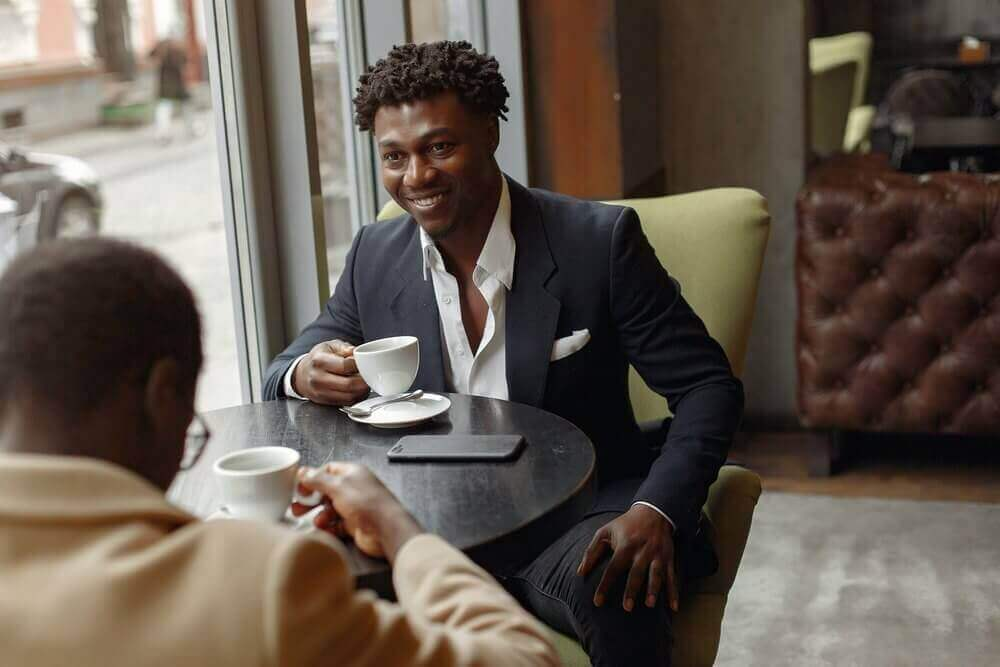 Two business men drinking coffee | Guide My Growth