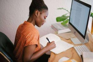 Woman writing | Guide My Growth