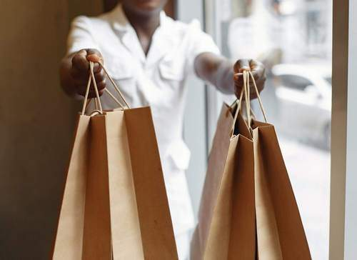 Person handing over shopping bags | Guide My Growth
