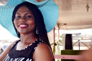 Smiling lady wearing a blue hat | Guide My Growth