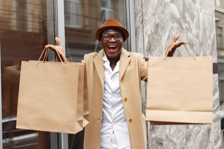 Man holding paper bags | Guide My Growth