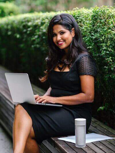 Smiling lady working on a laptop outdoors | Guide My Growth