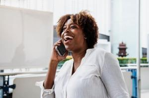 Laughing woman talking on phone | Guide My Growth