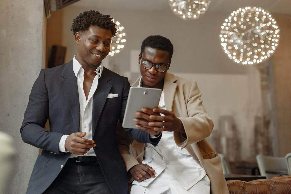 Businessmen looking at a tablet | Guide My Growth
