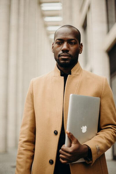 Man holding laptop | Guide My Growth