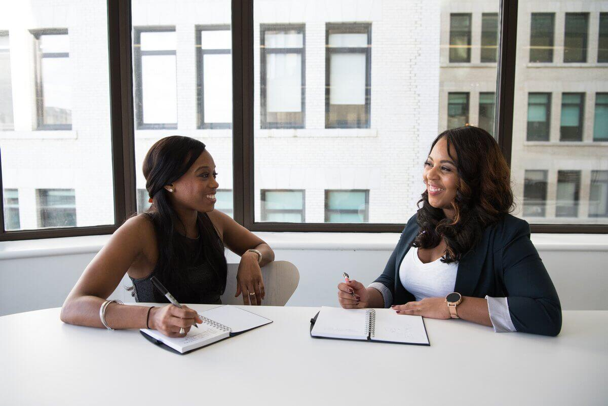 Business women at a table | Guide My Growth
