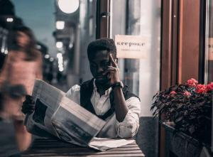 Man reading a newspaper | Guide My Growth