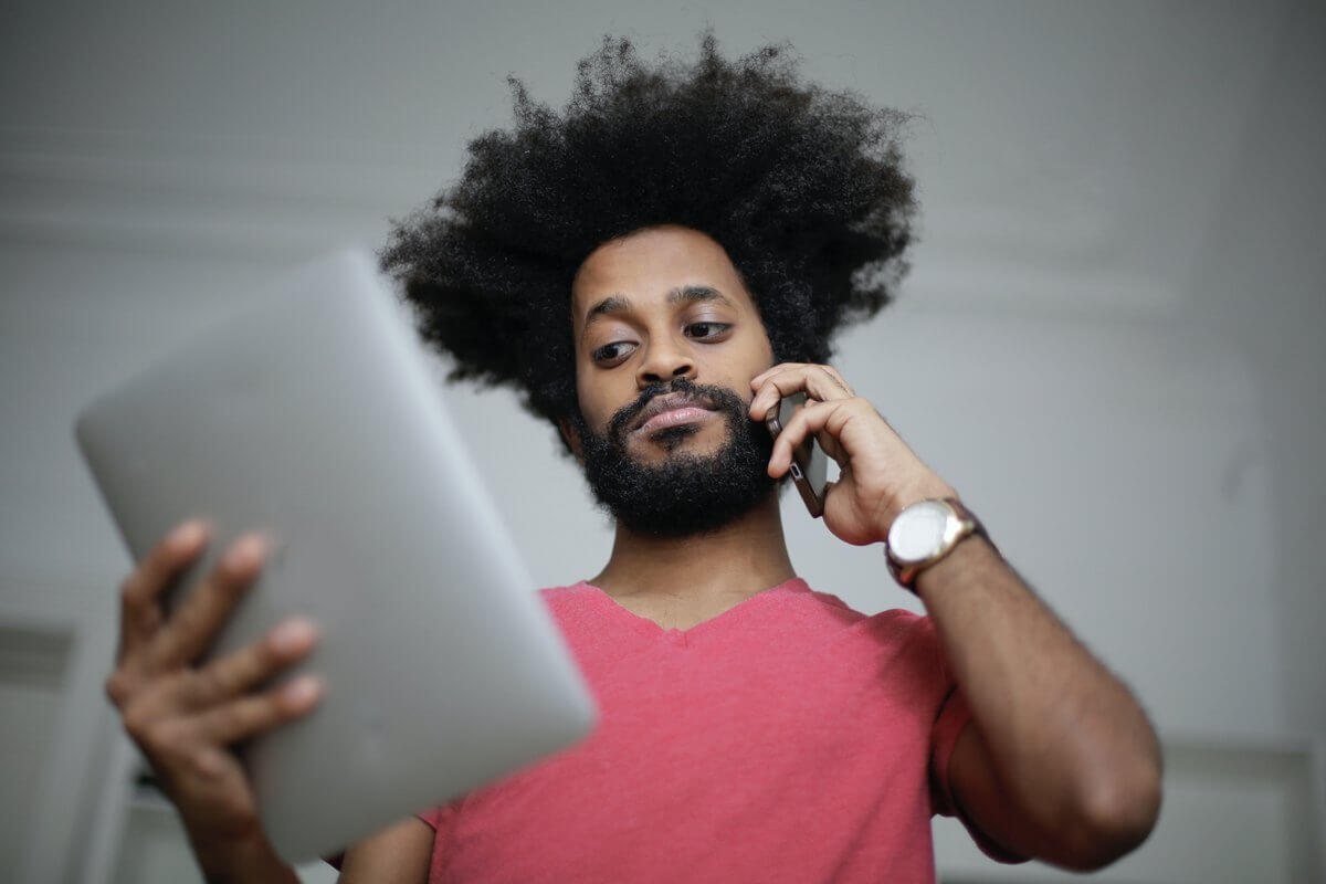 Man with phone and tablet | Guide My Growth