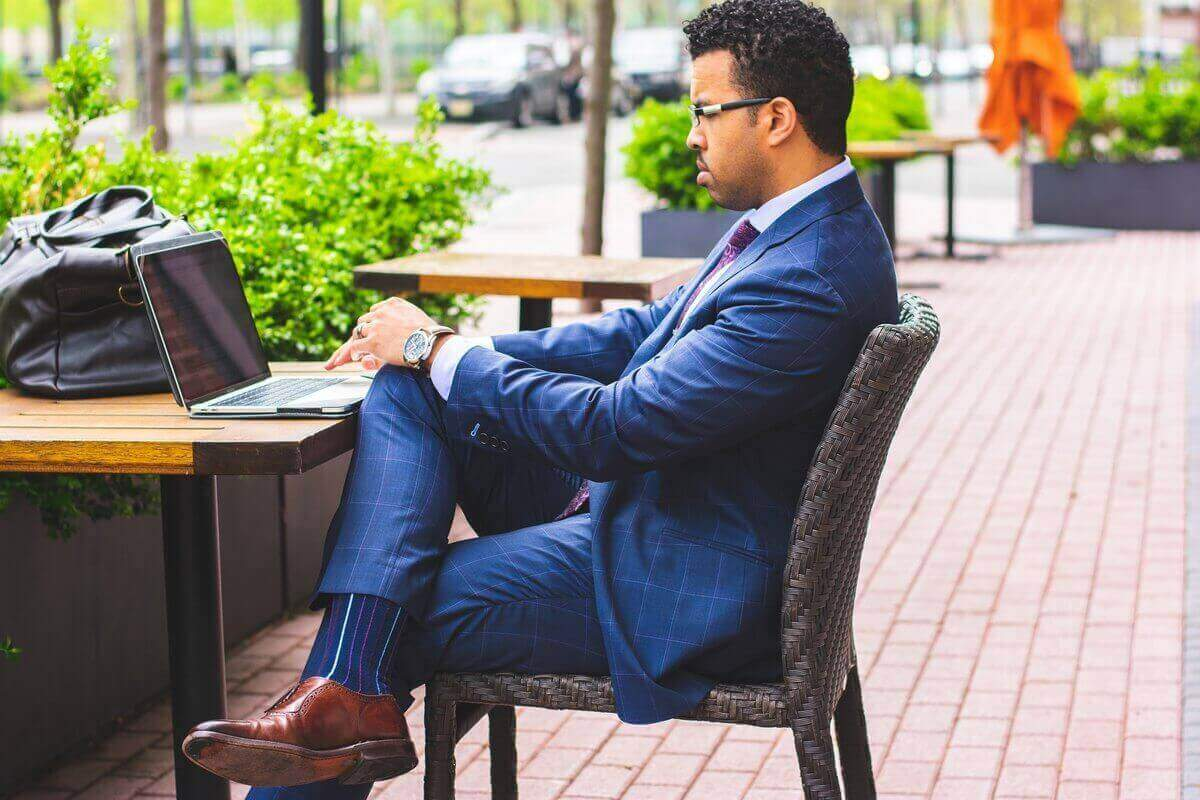 Man in suit at table with laptop | Guide My Growth
